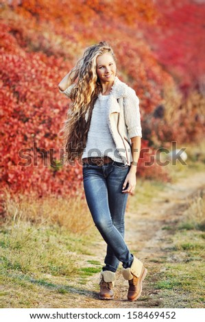 glamourous portrait of the fashionable young woman in an autumn landscape in leather boots - stock photo
