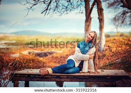 glamourous portrait of the young beautiful woman in leather boots on the bank of a lake on wooden pier - stock photo
