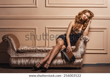 Glamourous portrait of the young beautiful woman in leather shoes and stylish handbag. Trend fashion look. Black dress. - stock photo