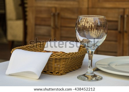glass and a basket of bread on a table on a white tablecloth