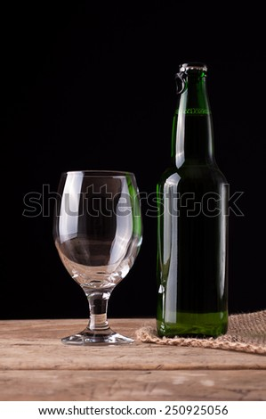 Glass And Bottle Of Beer on wooden table - stock photo