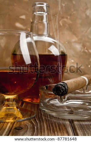 glass and bottle of cognac with a cigar on a wooden table - stock photo