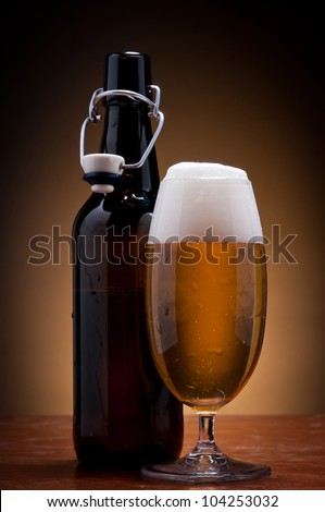 glass and bottle of fresh cold beer on a wooden table