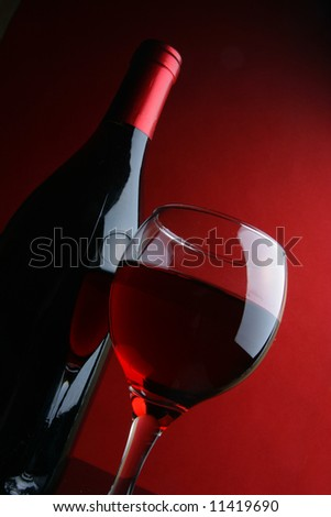 Glass and bottle of red wine over dark red background - stock photo