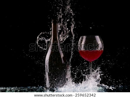 Glass and bottle of red wine splash on black