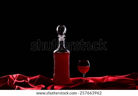 glass and bottle of wine on a dark background silk - stock photo