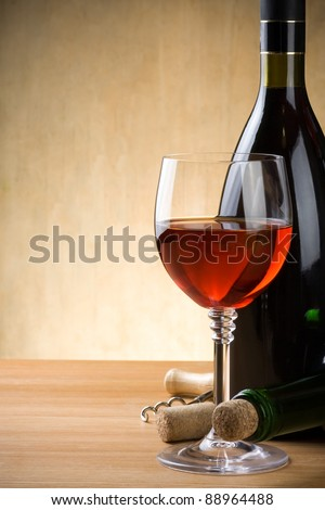 glass and bottle of wine on wood background - stock photo