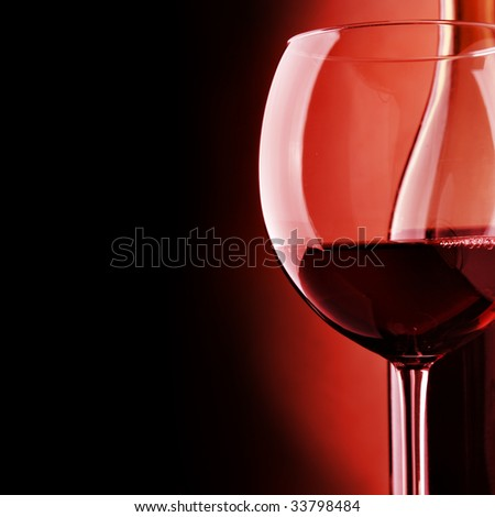 Glass and bottle of wine over black background - stock photo