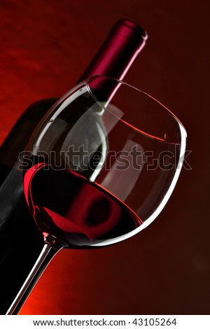 Glass and bottle of wine over red background - stock photo