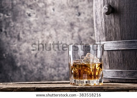 Glass and cask with old whiskey on wooden table - stock photo