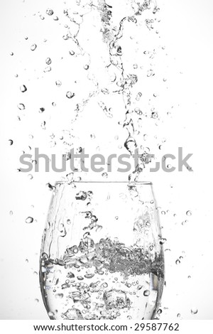 Glass and creative splashing water.Isolated on white