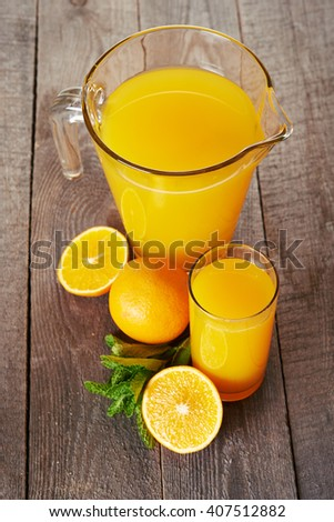 glass and pitcher of orange juice on wooden table - stock photo