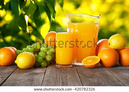 glass and pitcher with orange juice on wooden table. follage background
