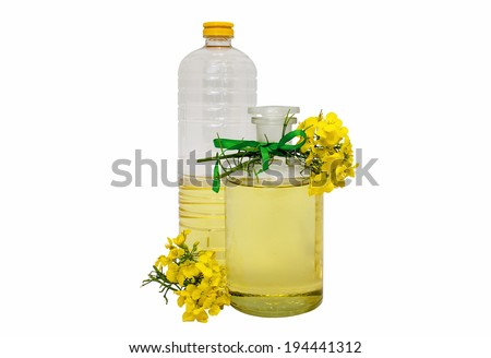 glass and plastic bottle of rape seed oil with rape flowers and ribbon  - stock photo