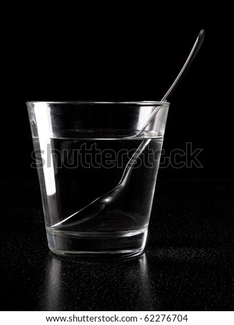 Glass and spoon with view of refraction in liquid - stock photo