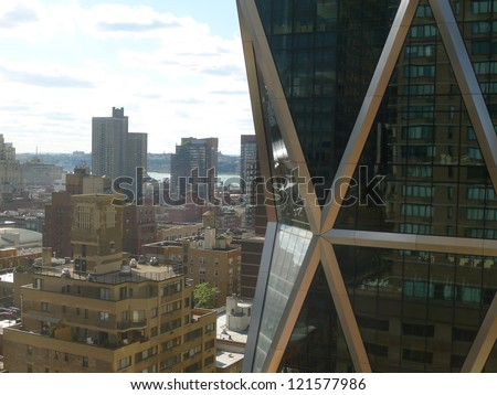 Glass and steel new york city skyscraper with views of manhattan looking towards the east river as shot from an adjacent 22nd floor building window - stock photo