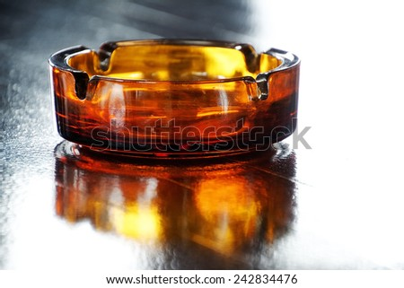 Glass ashtray on wooden table