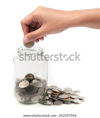 Glass bank for tips with money and hand isolated on white