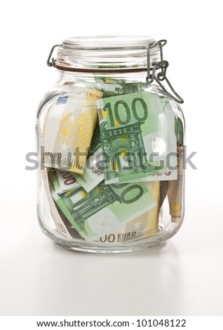 Glass bank for tips with money on white background
