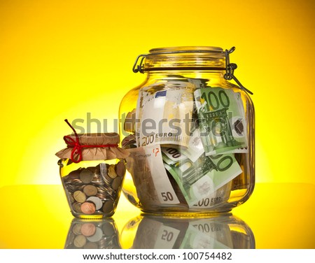 Glass bank for tips with money on yellow background - stock photo