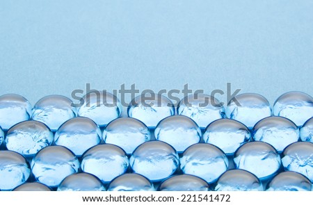 glass beads on blue background - stock photo