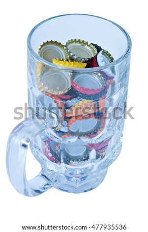 Glass Beer Mug and metal caps isolated on white background