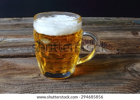 Glass beer on wood background, glass of fresh light beer