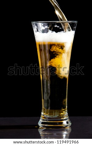 Glass being filled with beer against a black background - stock photo