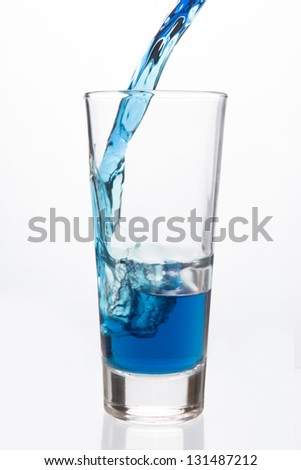 Glass being filled with blue liquid on white background
