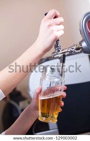 glass being filled with  by barman - stock photo