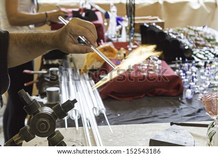 Glass blower working on crafts market, manufacture and workshop