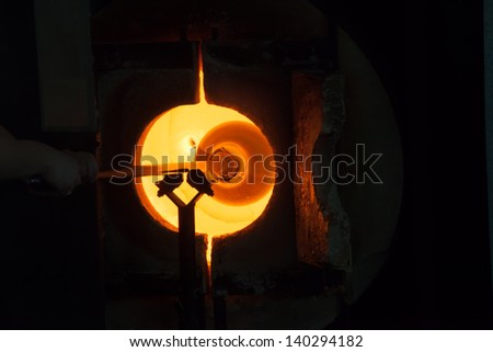 Glass blower, working with his glass creation on his pole in the furnace called the glory hole - stock photo