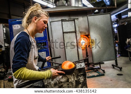 Glass Blowing Workshop - Two Women Shaping glass on the Blowpipe - stock photo
