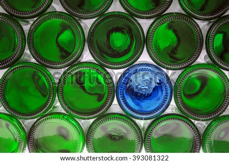 Glass blue bottle among green bottles. Concept of difference