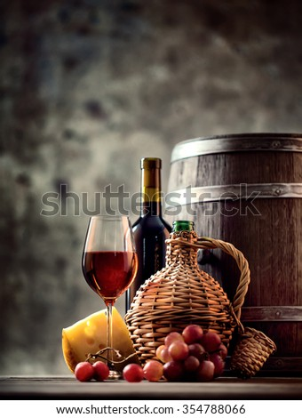 Glass, bottle, carafe of wine and barrel shot with selective focus - stock photo