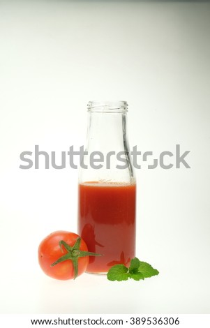 Glass bottle of fresh healthy juice with tomatoes isolated on white