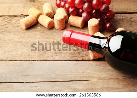 Glass bottle of wine with corks and grapes on wooden table background - stock photo