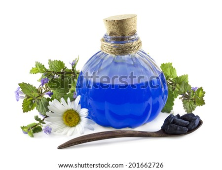 Glass bottle with blue healing remedy, chamomile and spoon with honeysuckle berries isolated on white - stock photo