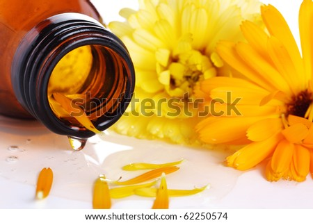 Glass bottle with drop of aromatic oil closeup - stock photo
