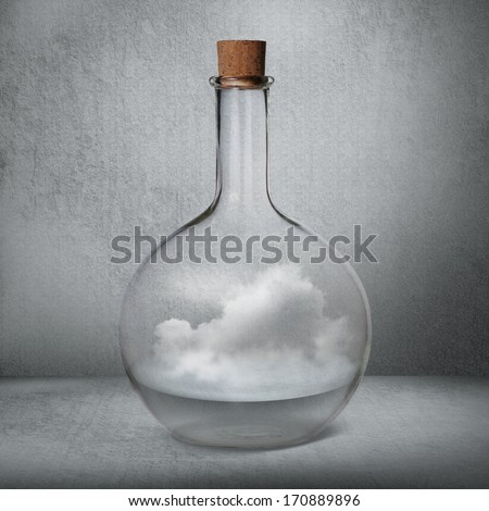 Glass bottle with liquid and vapor standing inside gray box - stock photo