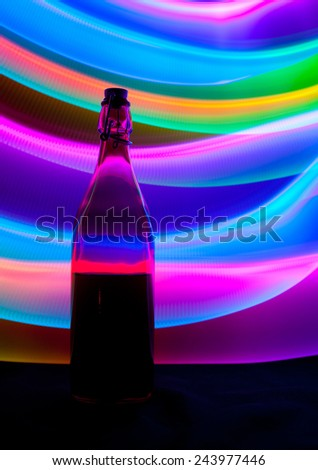 Glass bottle with sparks and waves of light, lightpainting - stock photo