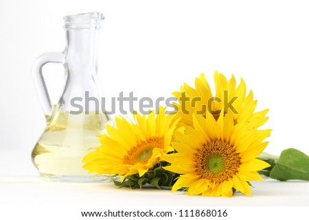 Glass bottle with sunflower oil and a sunflower isolated on white background - stock photo
