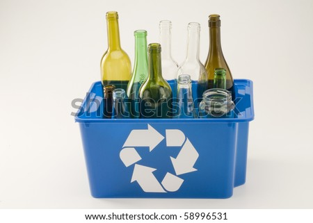 Glass bottles in a blue recycling bin. White background. - stock photo