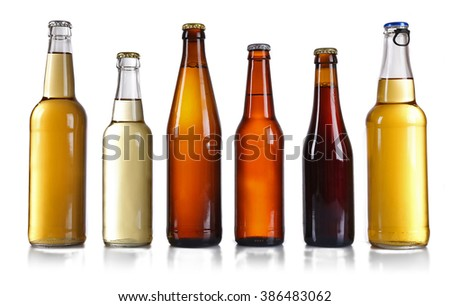 Glass bottles of different beer on light grey background