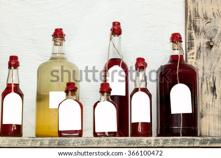 glass bottles of different sizes with liqueurs sealed with wax - stock photo