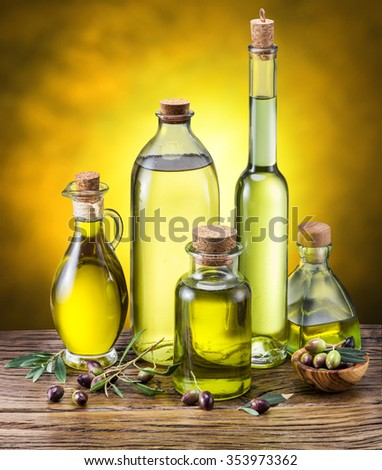 Glass bottles of olive oil and few berries on the wooden table. Studio shot. - stock photo