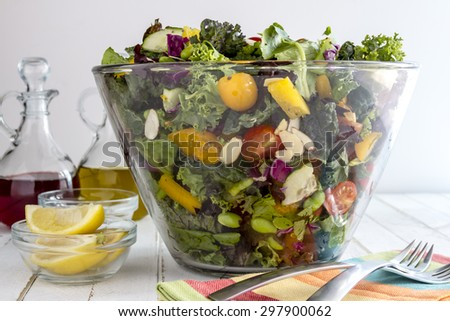 Glass bowl filled with organic super food salad with olive oil, red wine vinegar and forks - stock photo