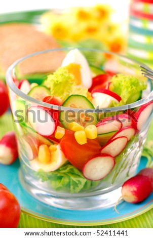 glass bowl of fresh salad with eggs and spring vegetables