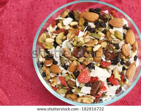 Glass bowl of healthy fruit and nut variety mix of strawberry, blueberry, black currants, dates, pumpkin seeds, pine nuts, almonds, coconut, walnuts, pistachio, raisins, sesame seeds, and pine nuts.  - stock photo