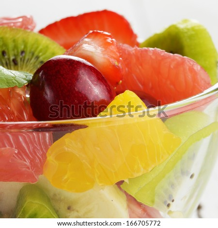 Glass bowl with mixed fruit salad on the white table - stock photo